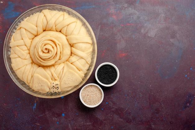 Vista dall'alto pasta per torta cruda rotonda formata sulla scrivania viola scuro