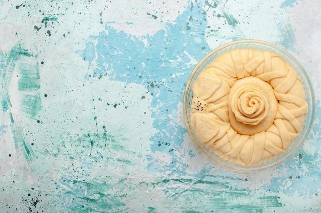 Вид сверху сырого теста для пирога, круглого, сформированного на синем столе