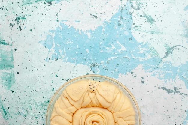 Вид сверху сырое тесто для пирога, круглое, сформированное на синей поверхности
