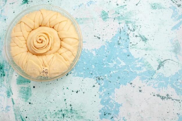 Вид сверху сырое тесто для пирога, круглое, сформированное на голубой поверхности