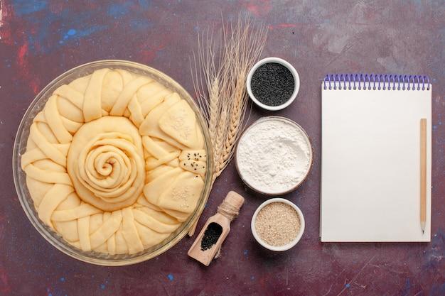 濃い紫色の机の上に調味料とメモ帳で形成された上面図生パイラウンド