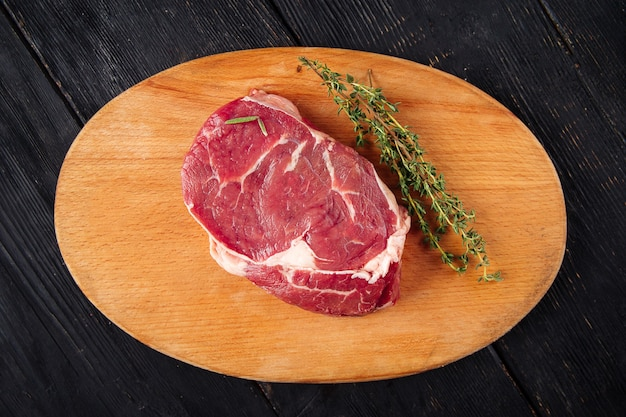 Top view on raw piece of meat with rosemary
