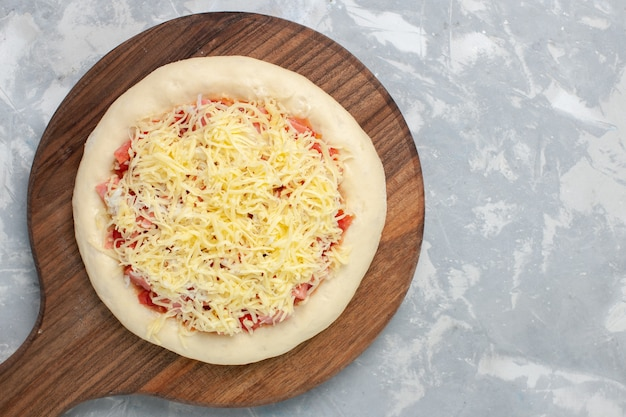 Top view raw pizza with cheese before going into the oven on white