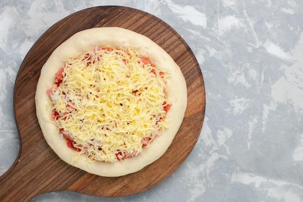 Вид сверху сырой пиццы с сыром перед тем, как пойти в духовку на белом