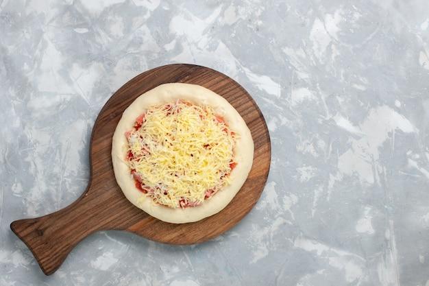 Pizza cruda vista dall'alto con formaggio su bianco