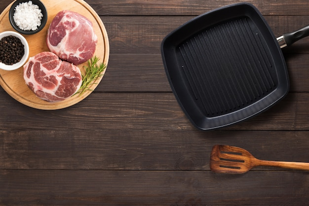 Top view raw pork chop steak, grill pan and spatula on the wooden background. copyspace for your text