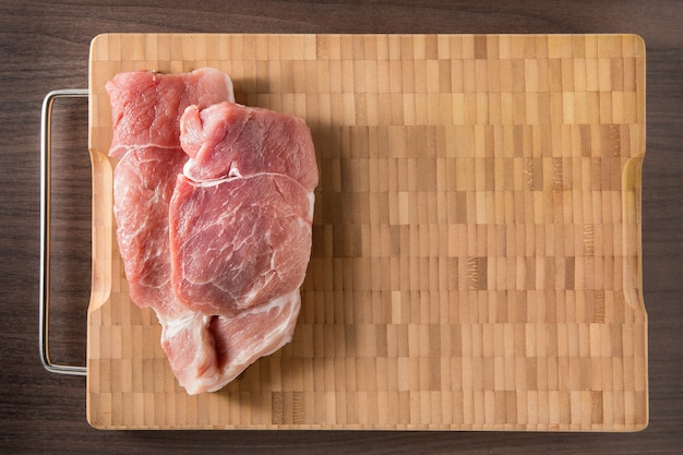 Top view raw pork chop steak on wooden bamboo background with free text space.