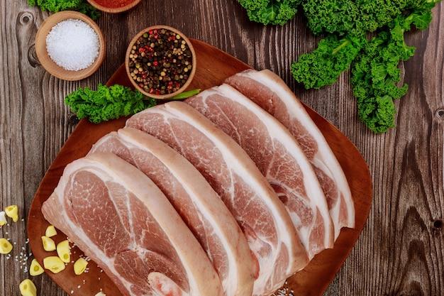 Вид сверху сырой свиной лопатки, нарезанной кожей и костью на деревянном столе