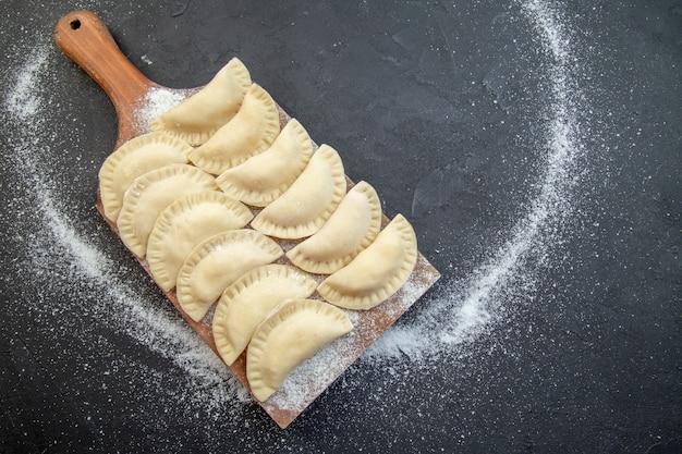 暗い背景の上の木の板の上のビュー生のジャガイモのホットケーキパイ生地調理ビスケットオーブンケーキ食品