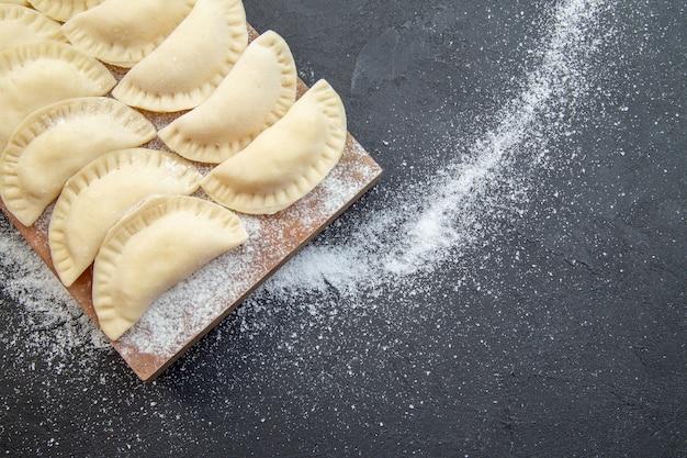 暗い背景の上の木の板の上のビュー生のジャガイモのホットケーキパイ生地調理オーブンケーキ食品焼き
