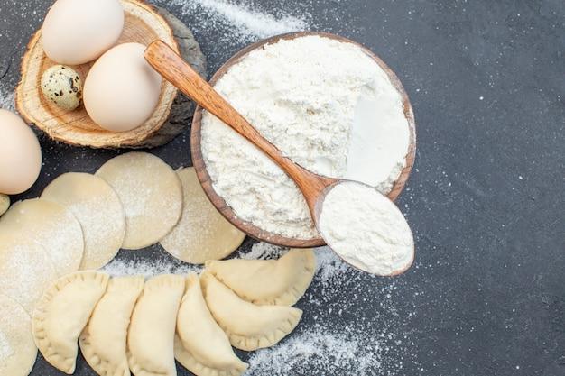 上面図暗い背景の食事パイビスケットオーブンケーキ焼き生地調理に卵と小麦粉と生のジャガイモホットケーキ