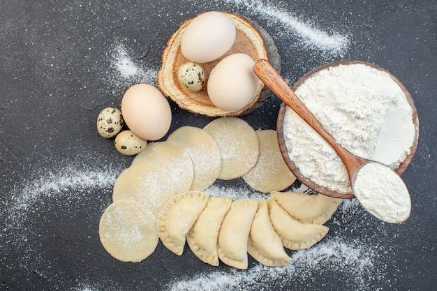 上面図暗い背景の食事パイ調理ビスケットオーブンケーキ焼き生地に卵と小麦粉と生のジャガイモホットケーキ