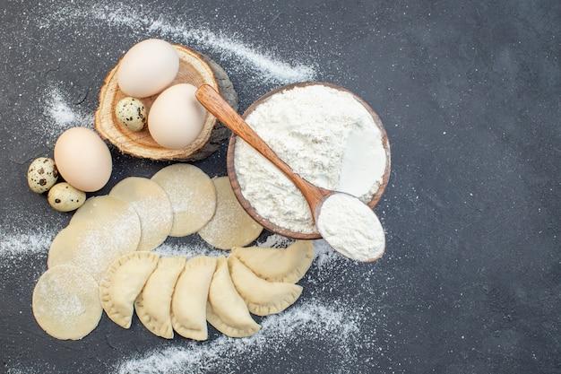 上面図暗い背景の食事パイ調理オーブンケーキ焼き生地に卵と小麦粉と生のジャガイモホットケーキ