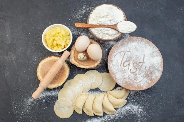 上面図生のジャガイモのホットケーキ、卵、マッシュポテト、小麦粉、暗い背景の食事パイビスケットオーブンケーキ焼き生地調理
