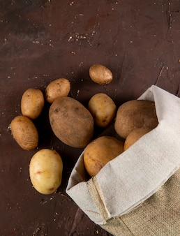 Top view raw potatoes in the bag on brown background