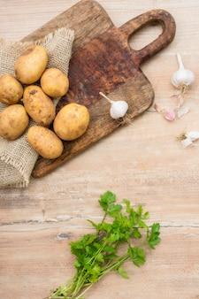 Вид сверху сырой картофель на деревянной доске