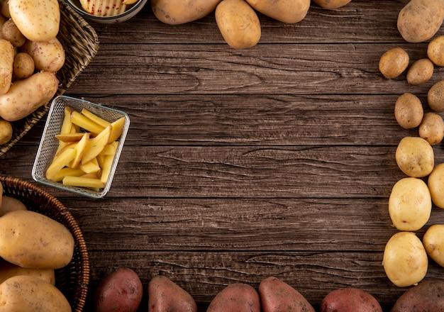 トップビュー木製の背景にコピースペースを持つ生のジャガイモの赤とみじん切りのジャガイモ