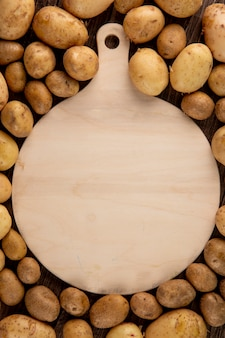 Top view raw potatoes with copy space on wooden background