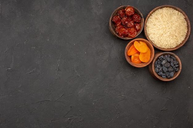 Vista dall'alto di riso crudo all'interno del piatto di legno con uvetta sulla superficie grigia