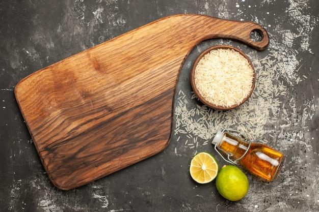 어두운 표면 원시 음식 과일 색상에 레몬과 기름으로 상위 뷰 원시 쌀
