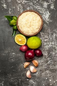 Vista dall'alto riso crudo con limoni cipolle e aglio su insalata matura cibo crudo superficie scura