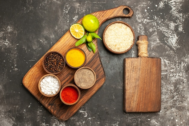 Top view raw rice with lemons and seasonings on dark surface raw food spice