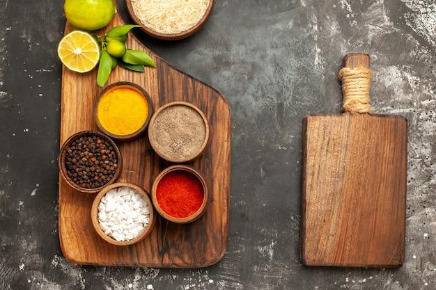 어두운 표면 향신료 과일 날 음식에 조미료와 레몬 상위 뷰 생 쌀