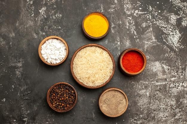 어두운 표면 향신료 날 음식에 조미료와 상위 뷰 생 쌀