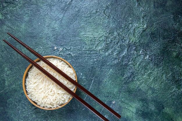 어두운 책상에 접시 안에 막대기와 상위 뷰 생 쌀