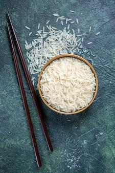 Вид сверху сырой рис с палочками внутри тарелки на темном столе