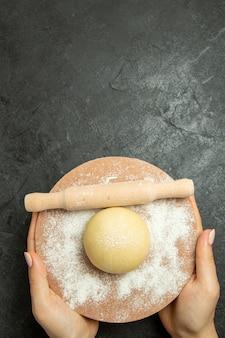 Vista dall'alto pasta rotonda cruda con farina sul cibo di farina di farina cruda di impasto grigio scrivania