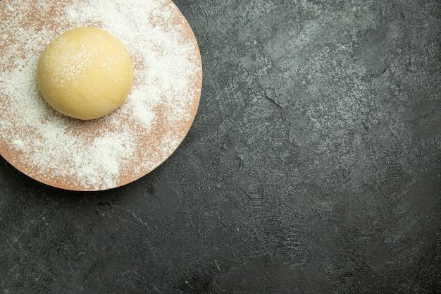 Вид сверху сырое круглое тесто с мукой на темно-сером настольном тесте сырая мука