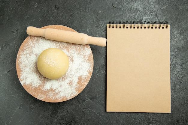 회색 배경에 밀가루와 상위 뷰 원시 라운드 반죽 반죽 원시 식사 밀가루 음식