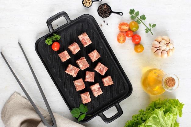 상위 뷰 원시 saikoro 와규 큐브 배경에 양상추와 함께 스테이크 접시에 쇠고기 스테이크, 배경에 다른 향신료와 함께 흰색 테이블 위에