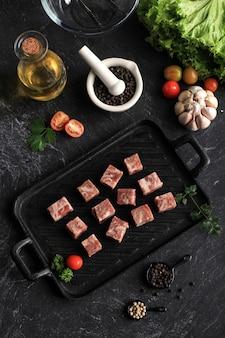검은 대리석 테이블 위에 양상추, 기름, 토마토 및 기타 향신료와 함께 스테이크 접시에 원시 saikoro 와규 큐브를 볼 수 있습니다. 일반적으로 냉동 판매, 즉석 조리 가능