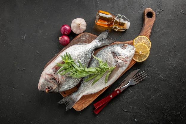 Vista dall'alto pesce di mare crudo sul tagliere forchetta e coltello bottiglia di olio cipolle gralic su nero