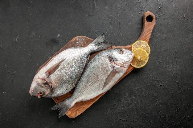 Вид сверху сырой морской рыбы, ломтики лимона на разделочной доске на черном