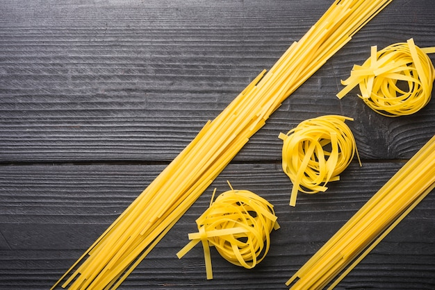 Top view of raw spaghetti between the tagliatelle on black wooden backdrop