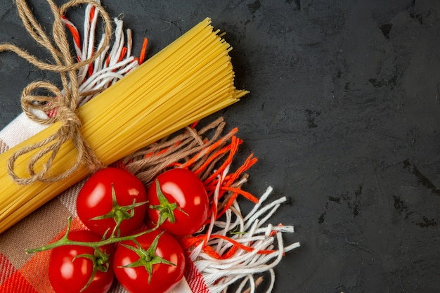 Top view of raw spaghetti and tied with string and fresh tomatoes on black