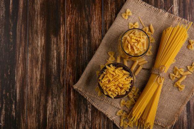 Top view of raw spaghetti with raw pasta on a beige napkin on a wooden surface