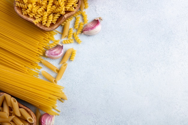Top view of raw spaghetti with raw pasta in bowls with garlic on a gray surface