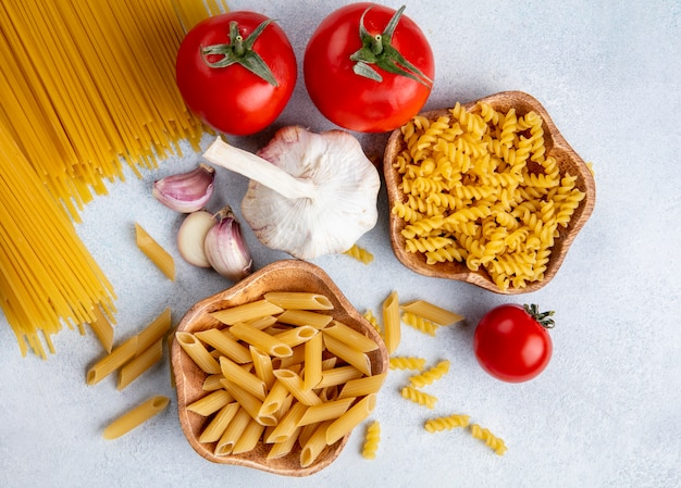 Top view of raw spaghetti with raw pasta in bowls with garlic and tomatoes on a gray surface