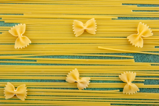 Top view of raw spaghetti with raw pasta on a green surface
