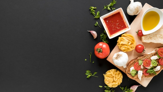 Top view of raw tagliatelle pasta; sandwich; with ingredients on background