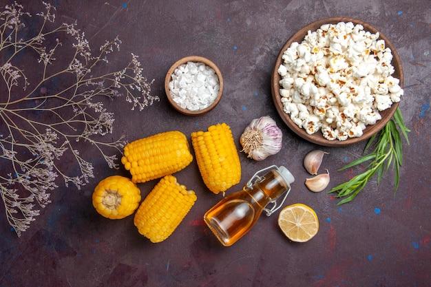 Vista dall'alto mais gialli crudi con popcorn fresco su superficie scura film popcorn snack pianta mais