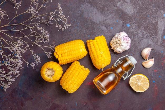 暗い表面のスナックポップコーン映画植物トウモロコシに油とレモンと生の黄色いトウモロコシの上面図