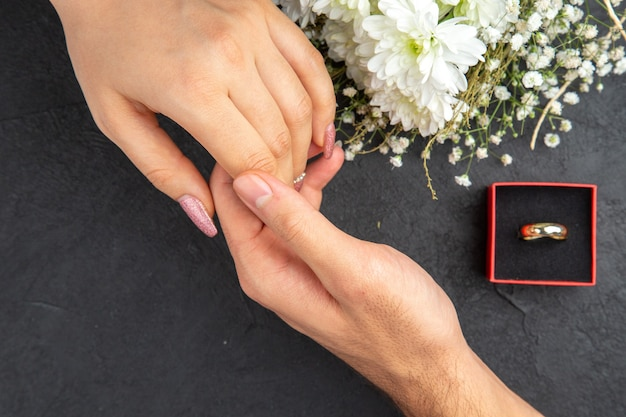 어두운 배경에 여성 손 약혼 반지 꽃 꽃다발을 들고 손 남성 손에 도달하는 상위 뷰