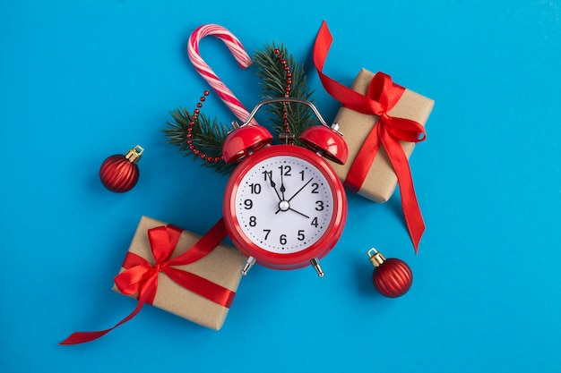 Top view of red alarm clock and christmas composition on the blue background. close-up.