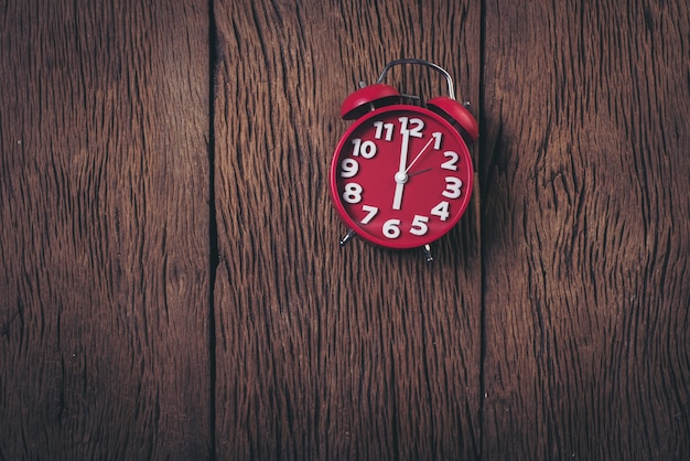 Top view red alarm clock on wood background