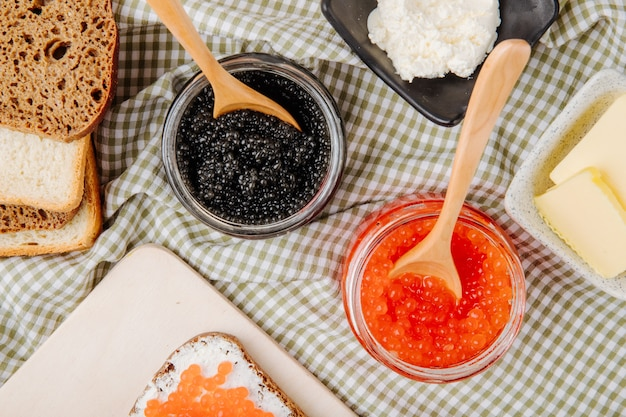 Вид сверху банку красной и черной икры с ржаным хлебом, белым хлебом, маслом и творогом на столе